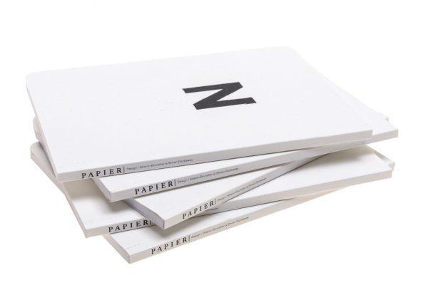 מחברת LETTERS עם כריכה לבנה ועליה אות אחת מאותיות ה-ABC מודפסת בשחור.